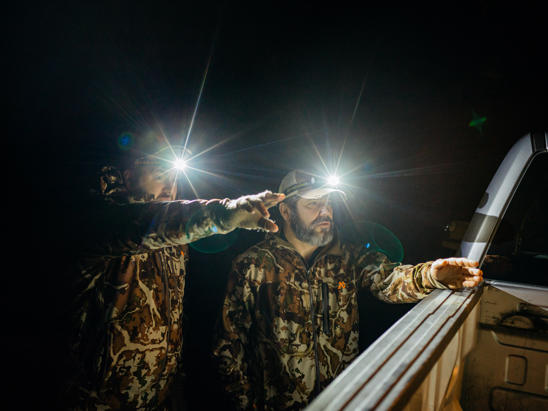 Deer Hunters at night with headlamps planning their hunt