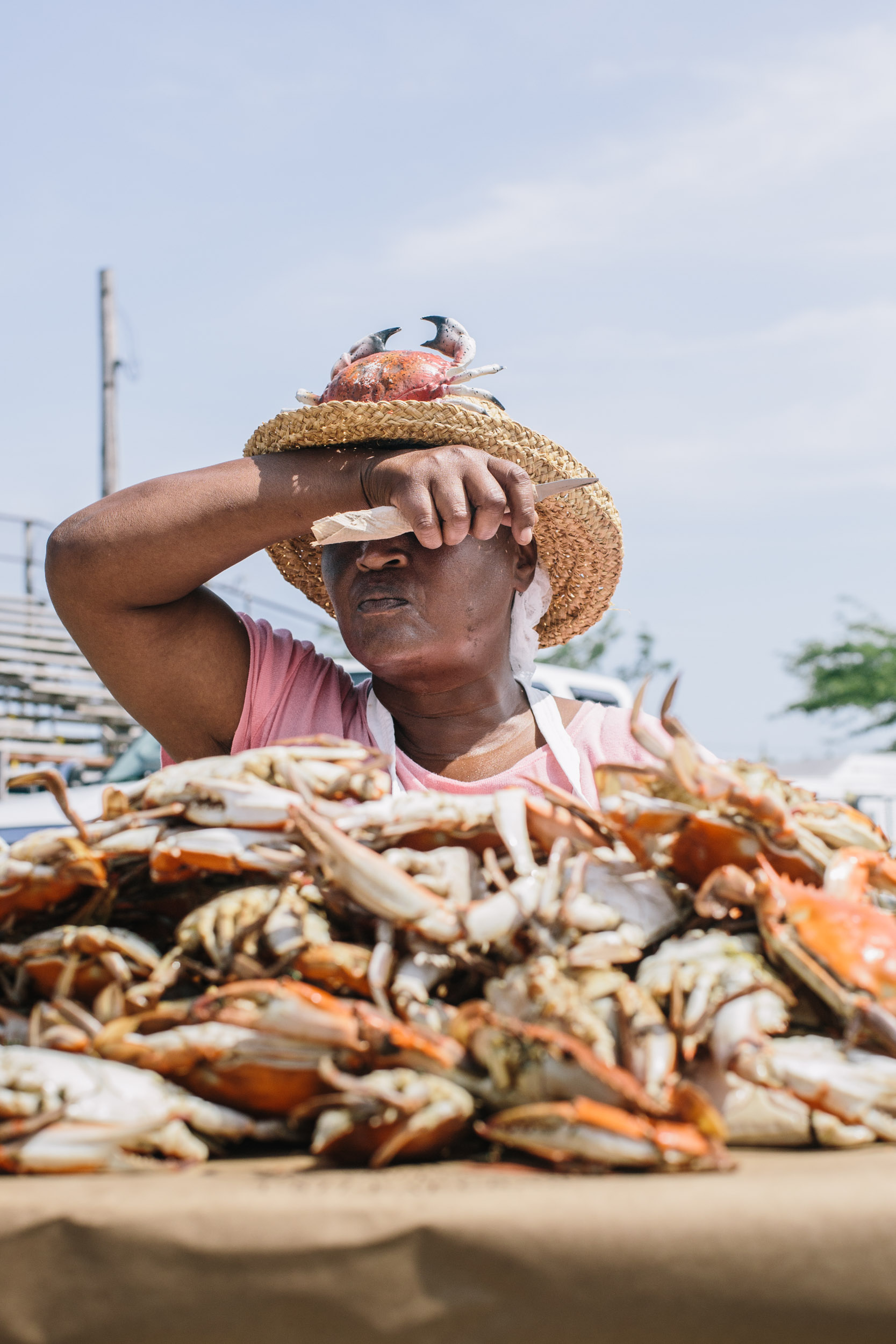 woman picks pile of blue crabs