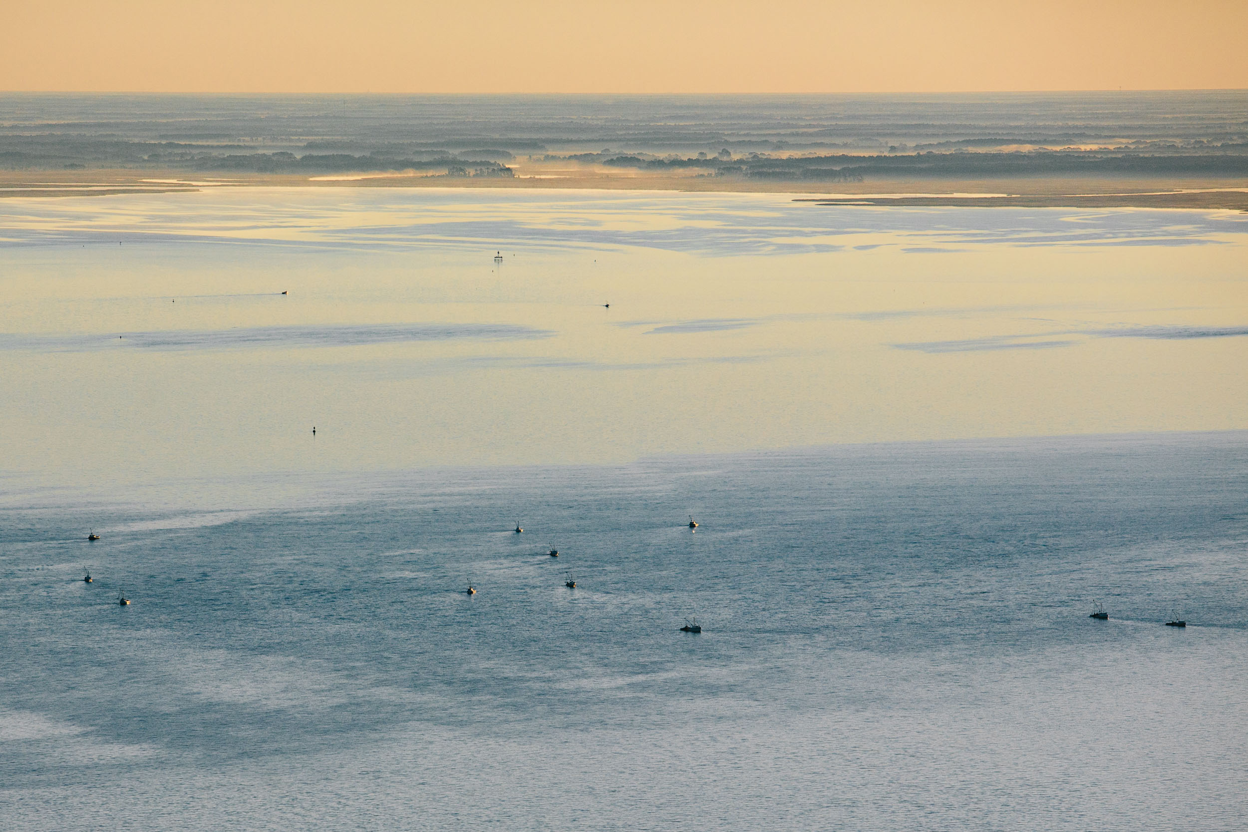 aerial photo of Crab boats at sunrise head out into the bay