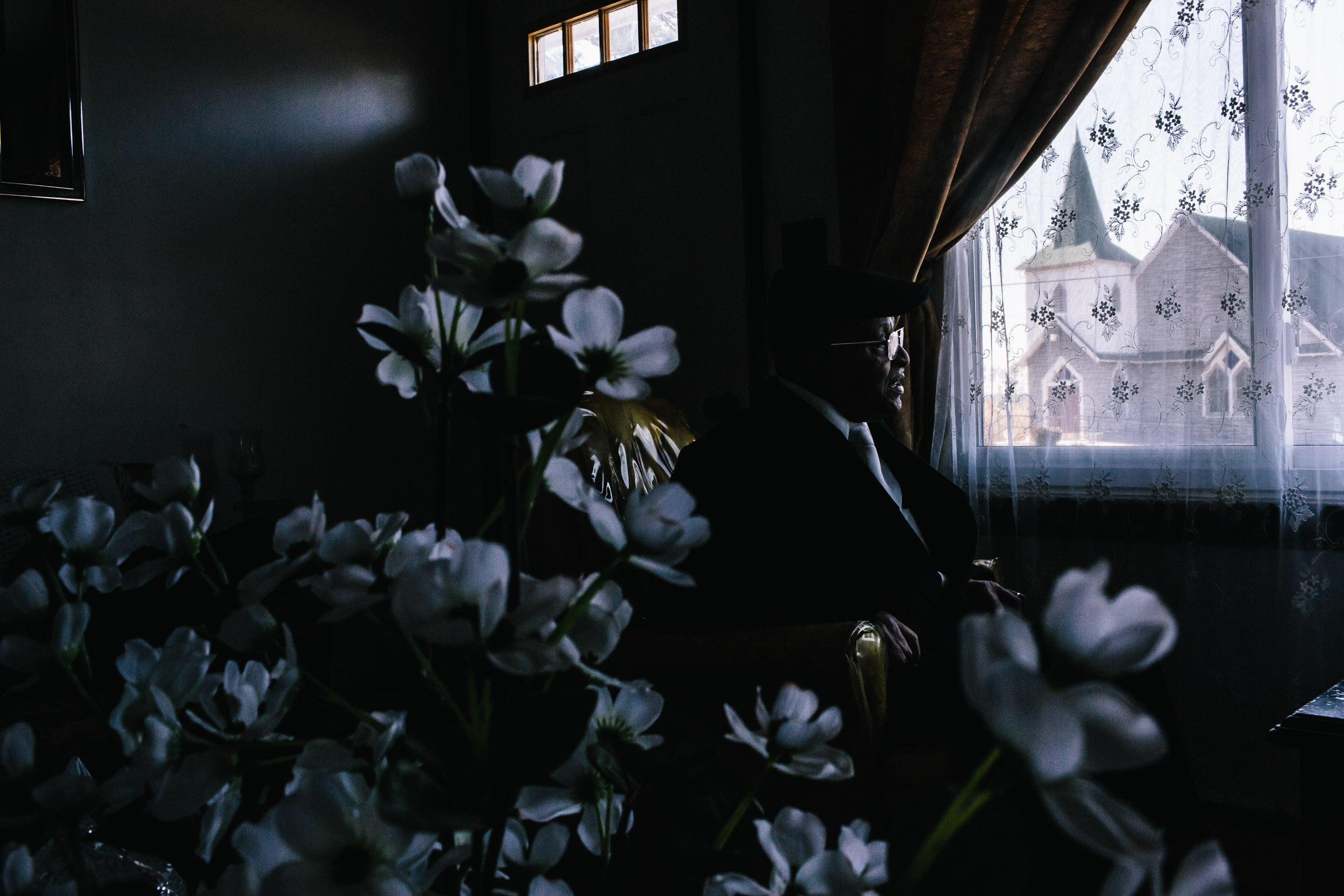 Washington DC editorial photographer man in living room across from historic church with flowers
