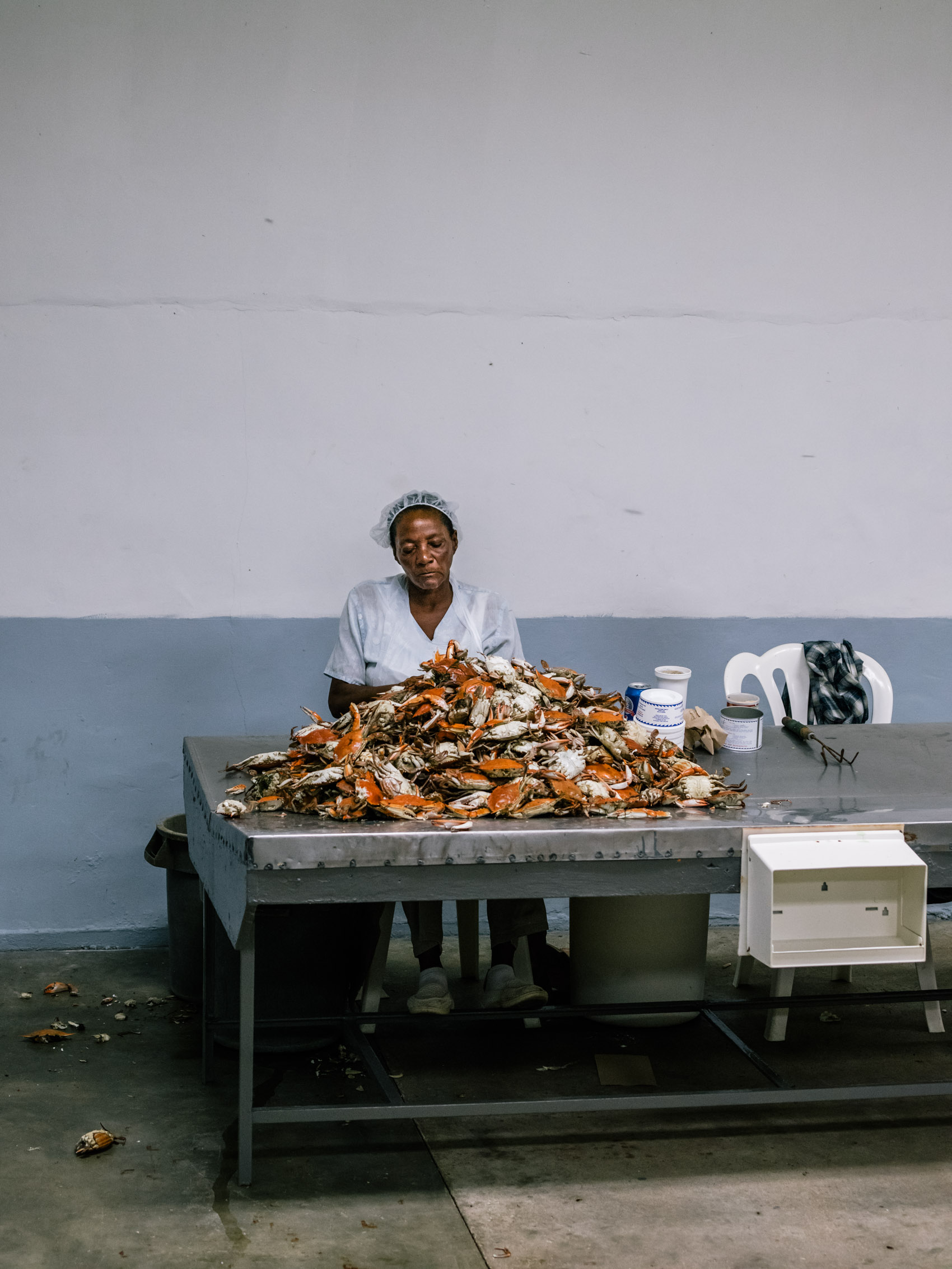 woman with pile of crabs to pick for meat at seafood house