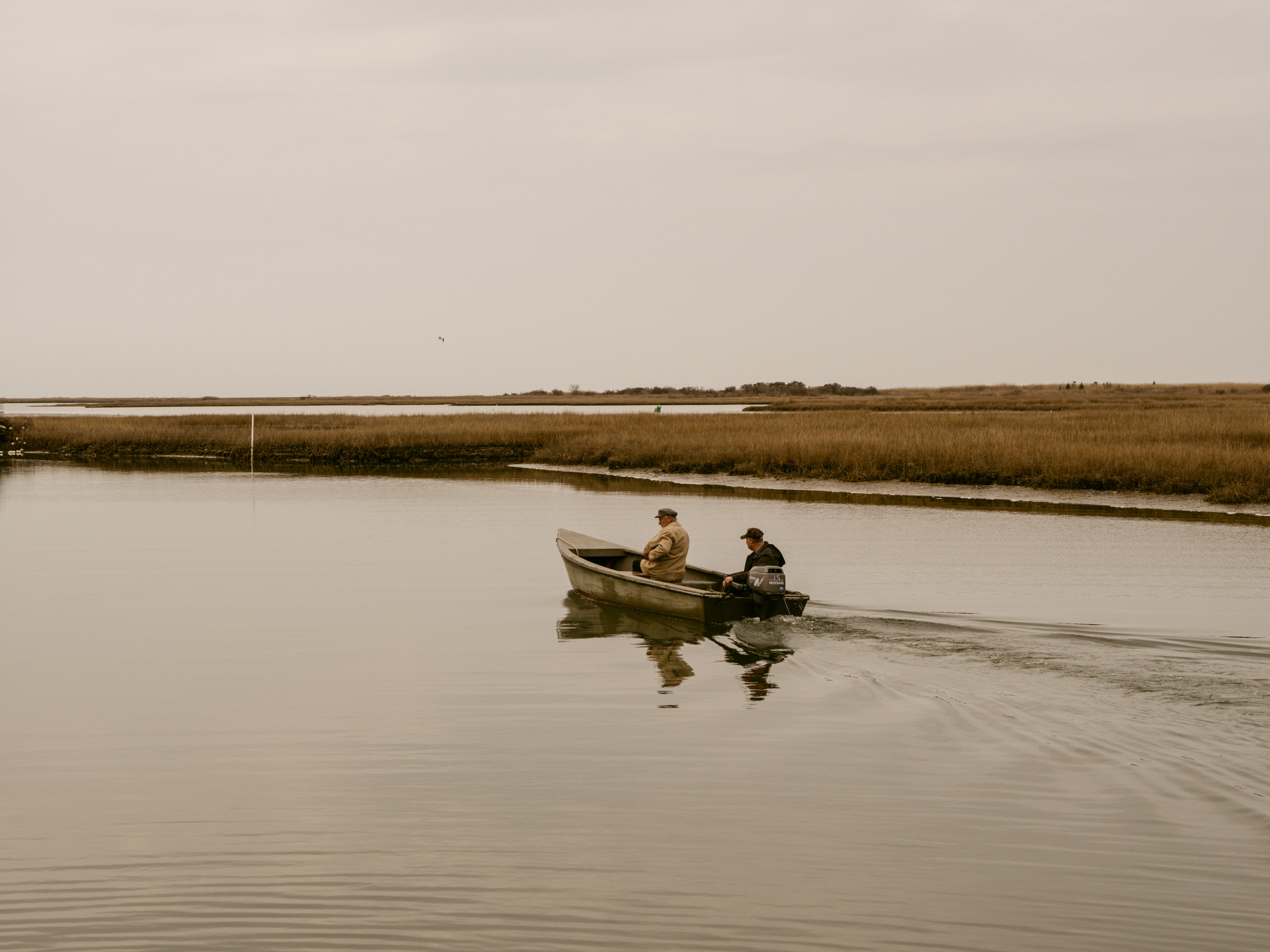 two men on boat in calm water through marsh