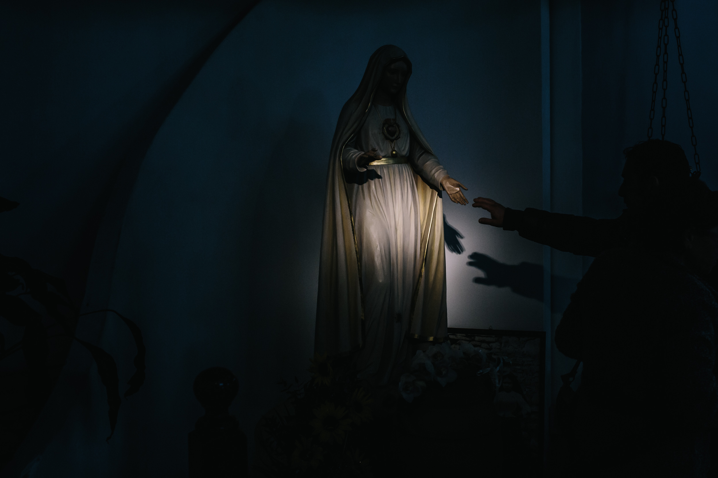person reaching out to touch hand of Virgin Mary statue at church