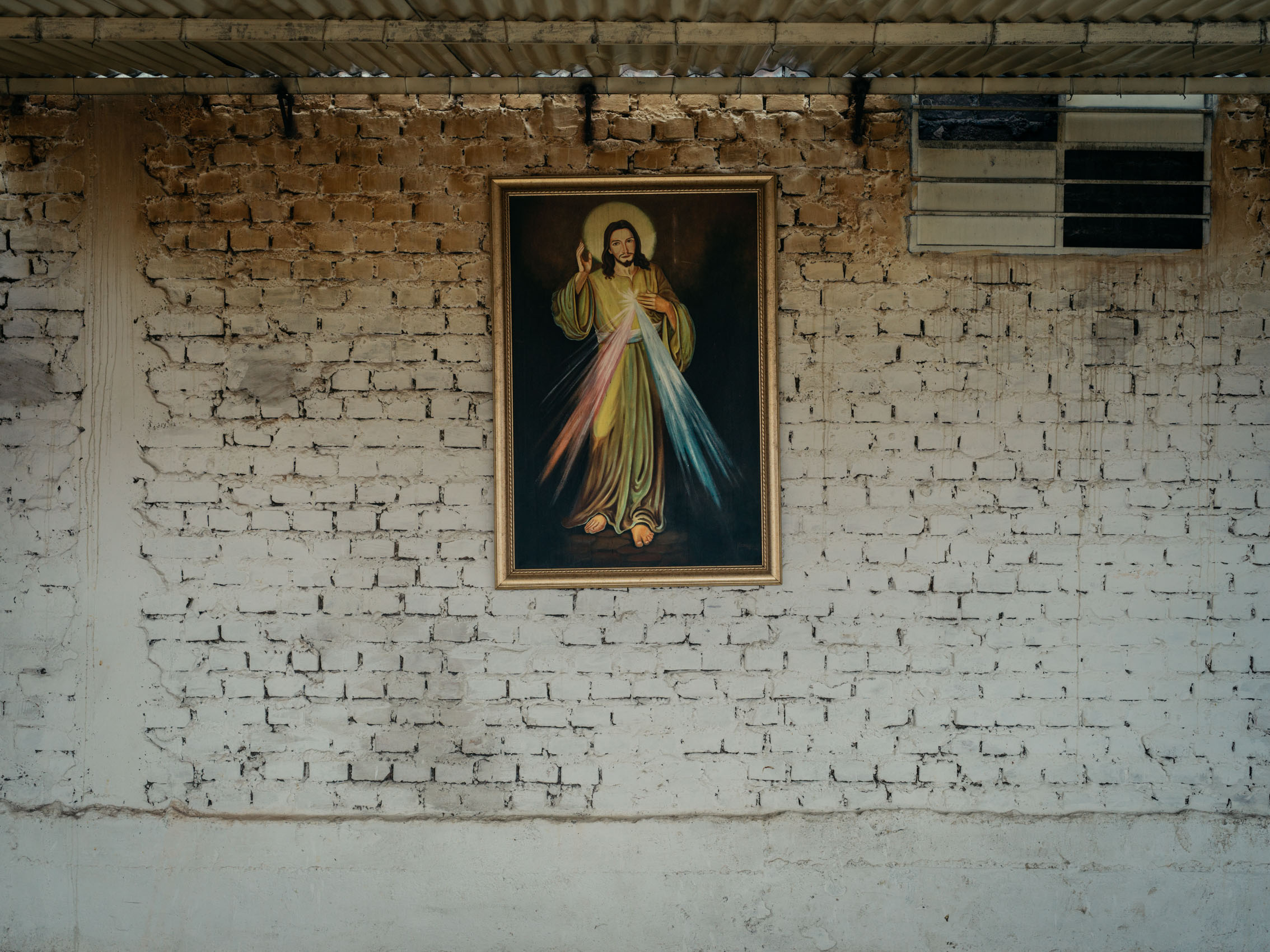 A painting of Jesus hangs on a white brick wall