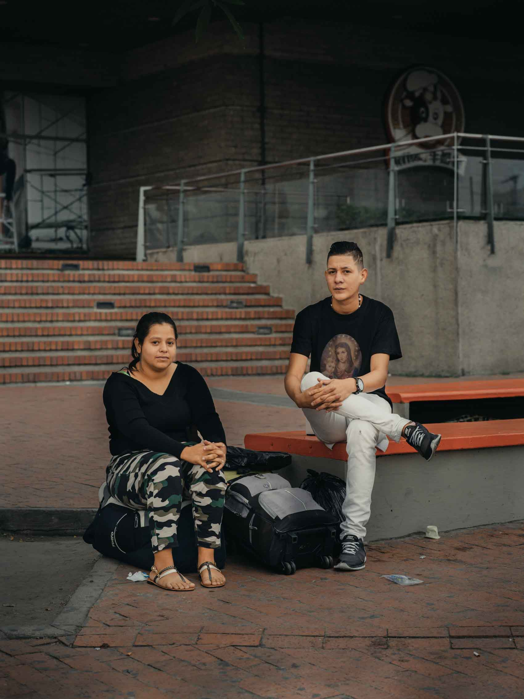 portrait of friends sitting on bench outside mall