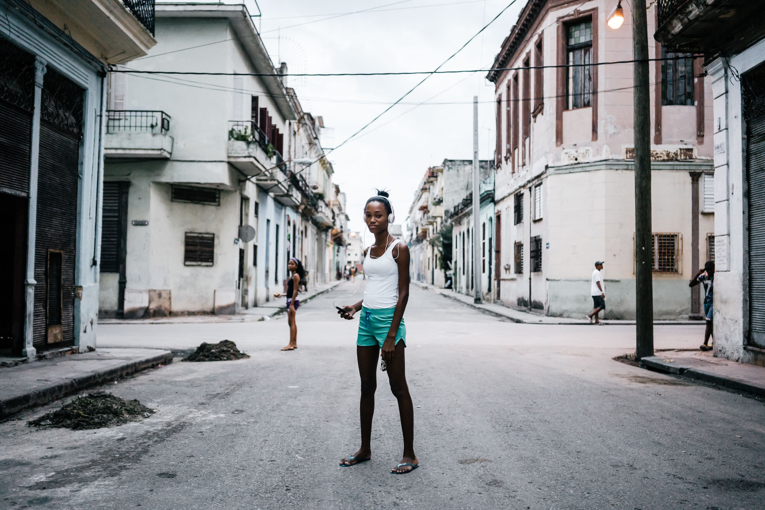 woman listens to music in streets of Havana
