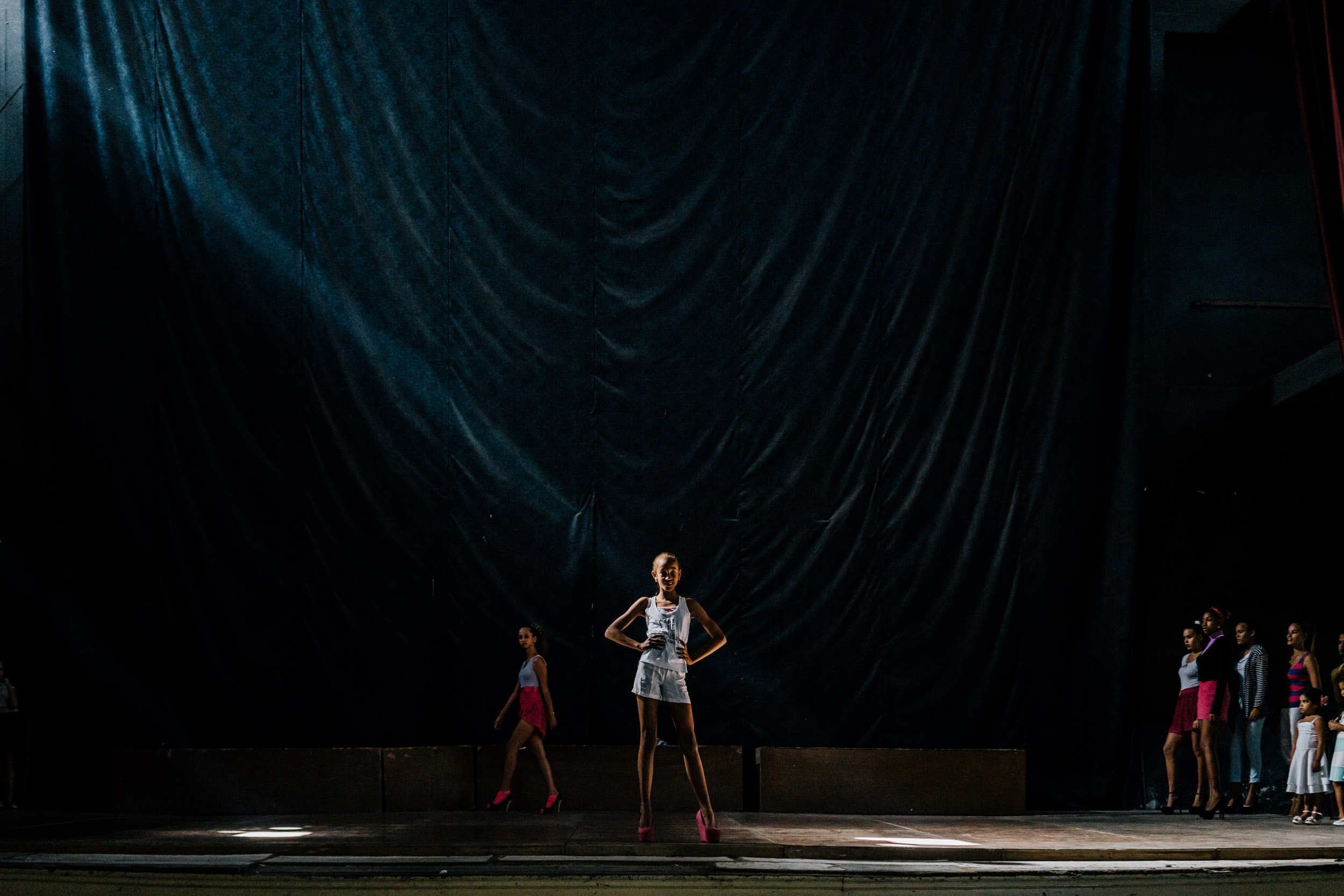 Modeling school attendees strut and pose on stage at the Teatro Municipal in Havana