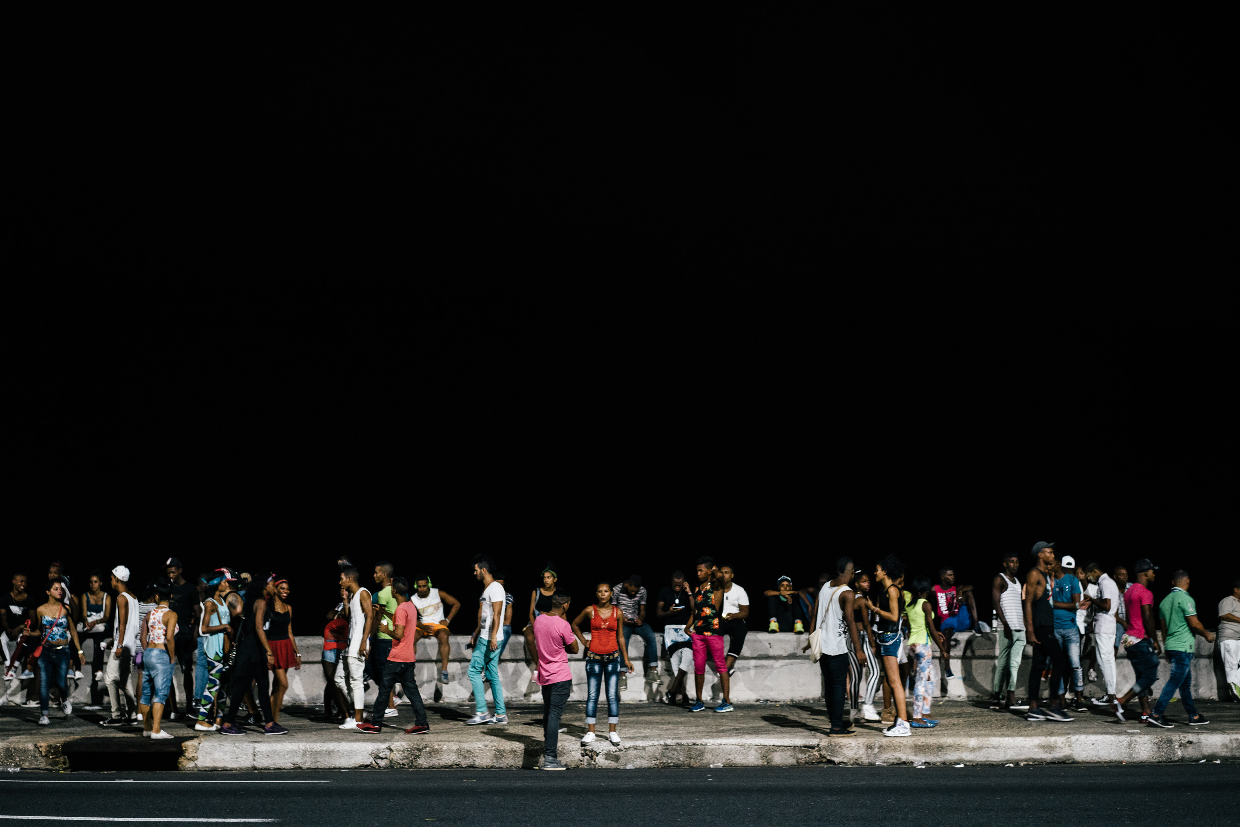 people partying at night along the Malecón in Havana