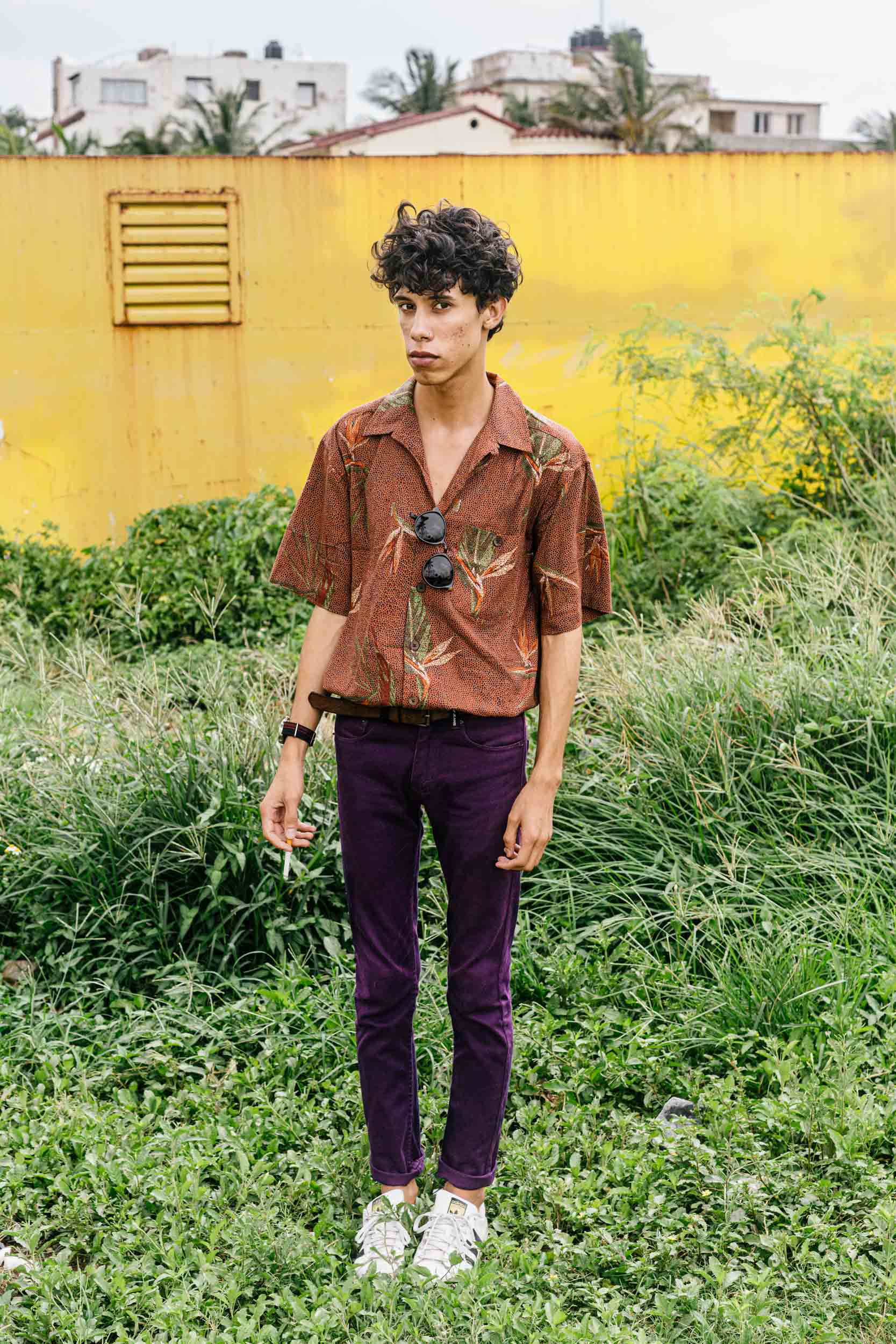 portrait of fashion blogger in purple pants with yellow wall