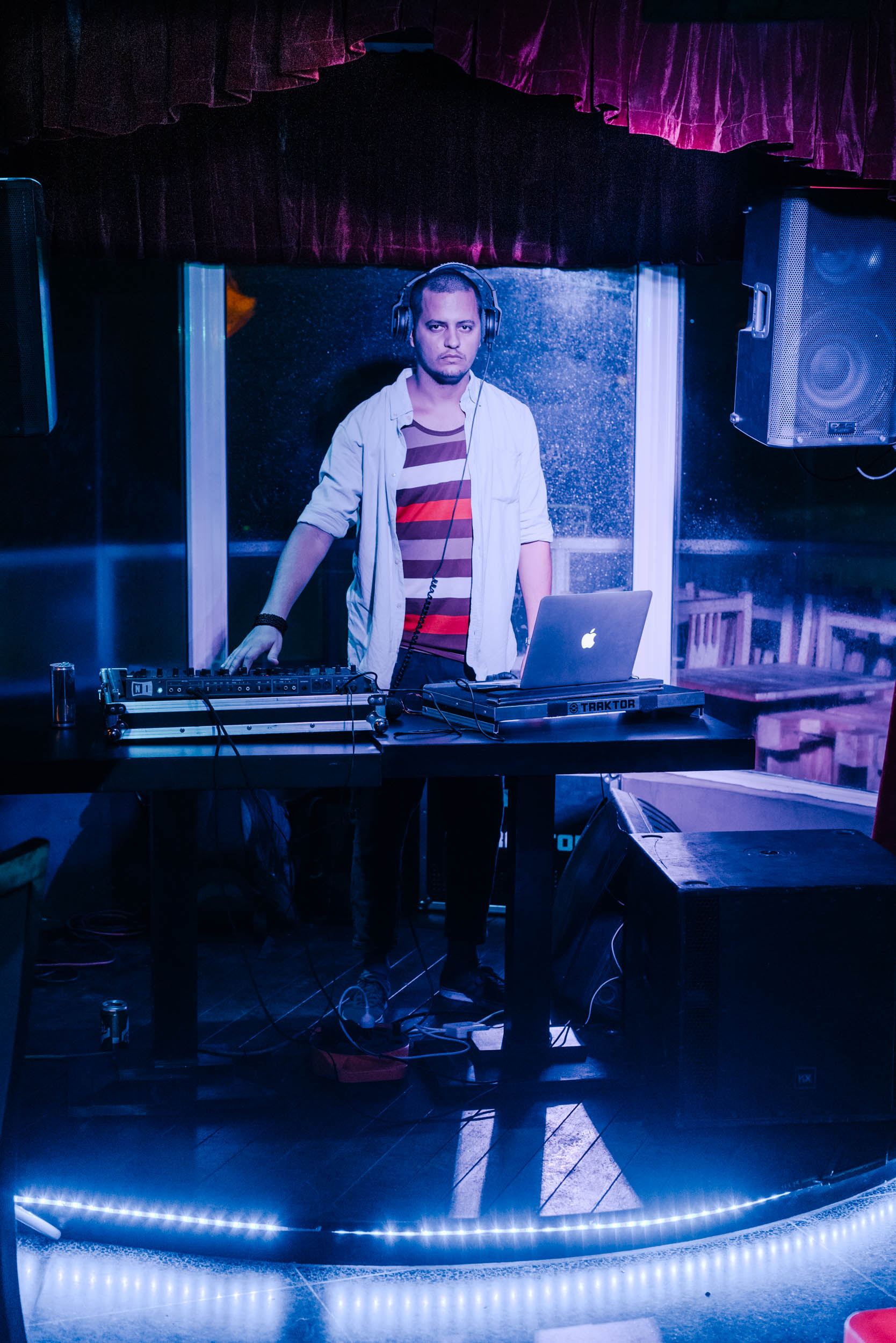 man standing at DJ booth inside dance club