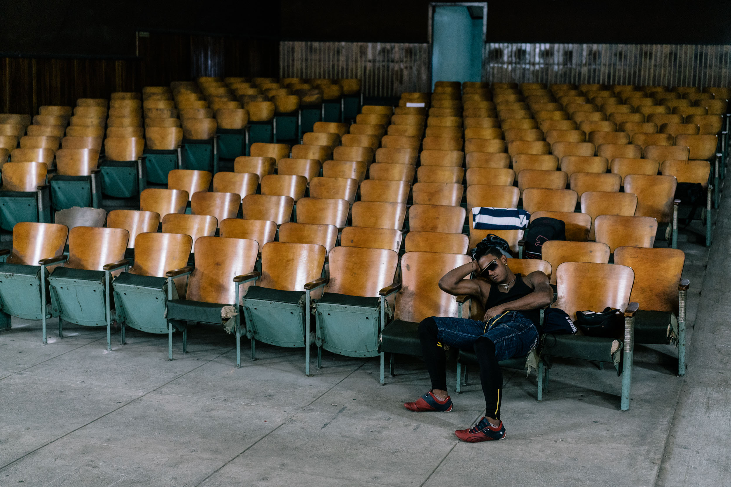 man asleep in chair in empty theater seats