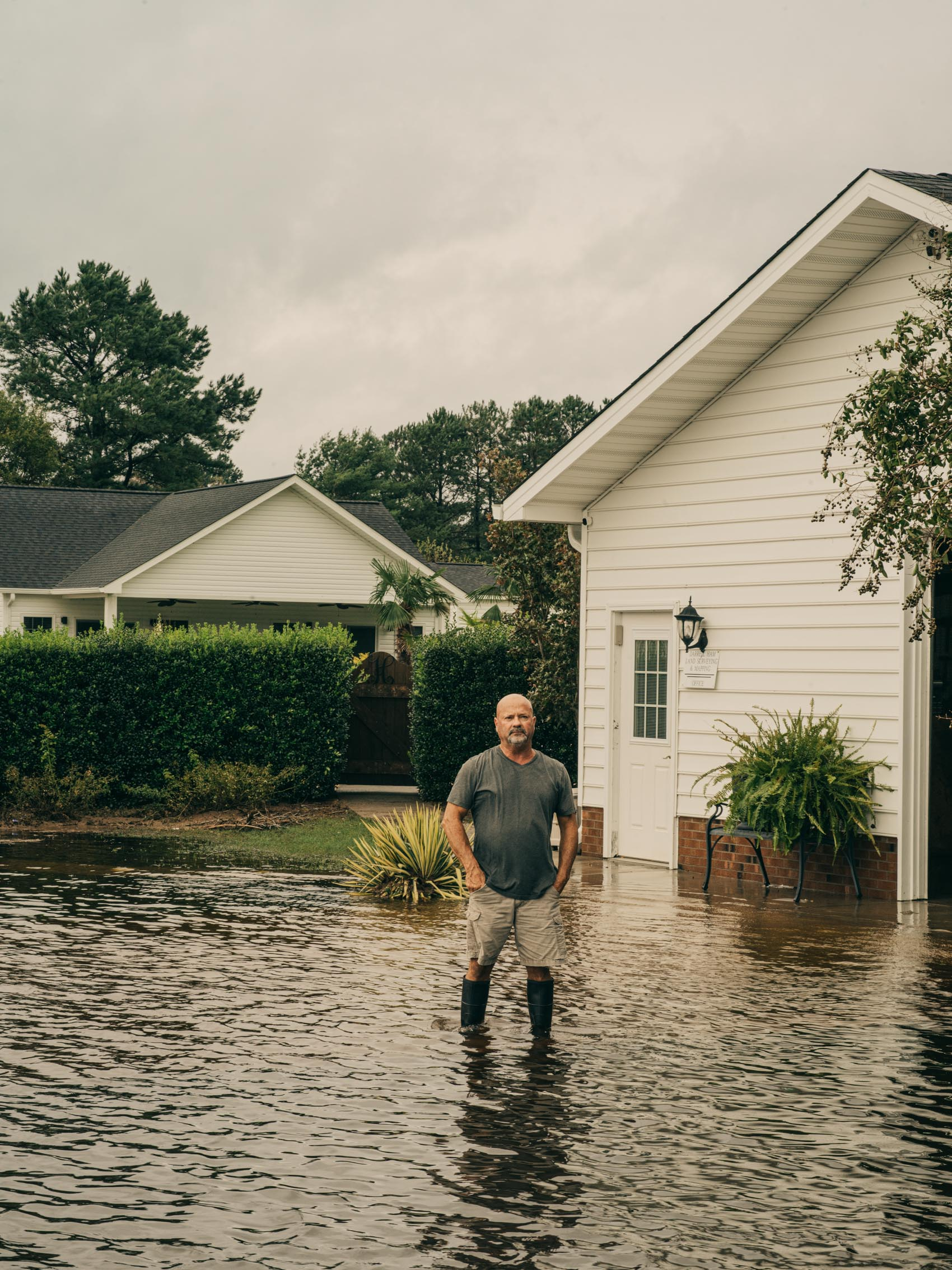Man stand in flooded front yard