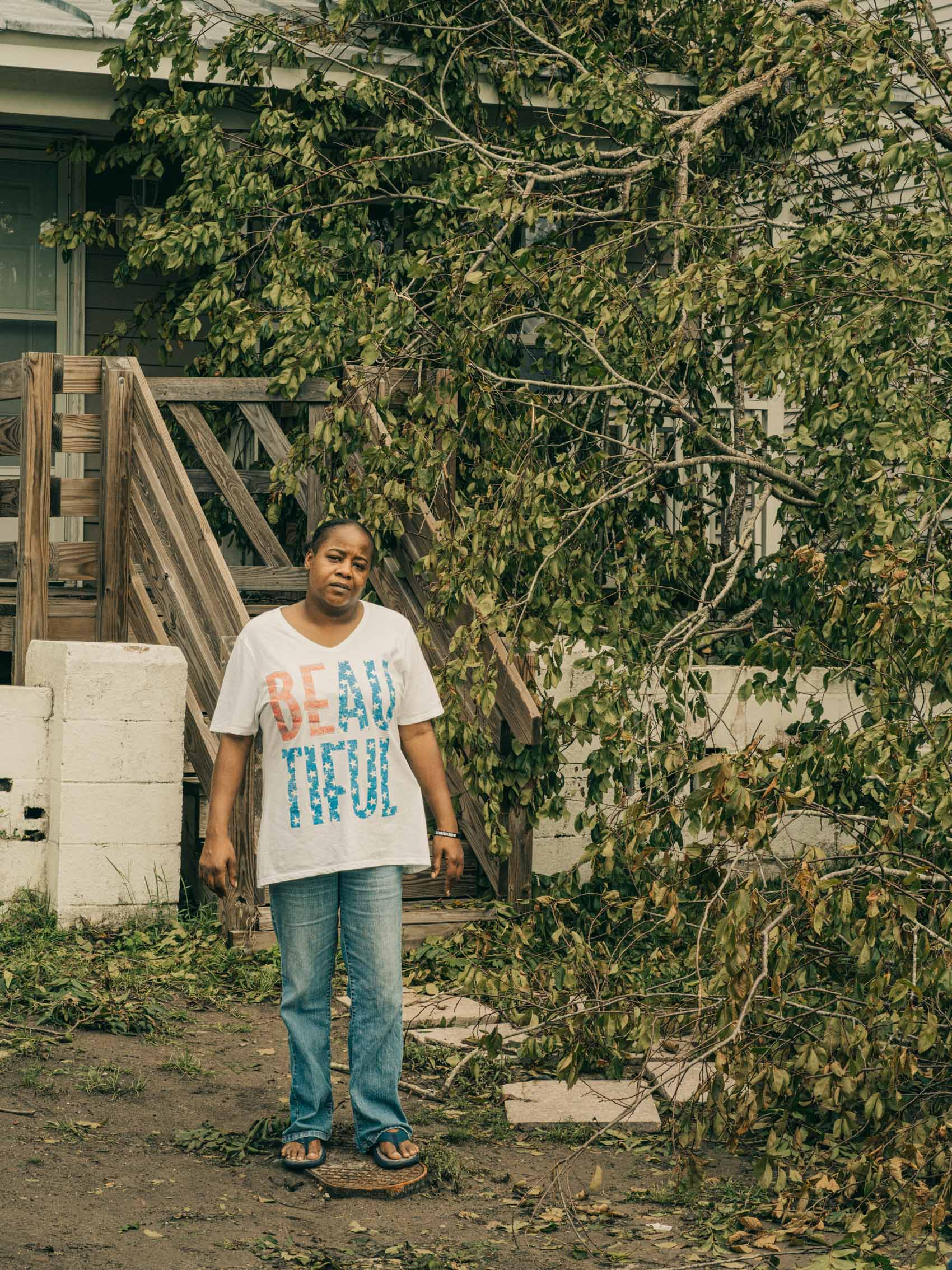 portrait of woman outside house with fallen tree