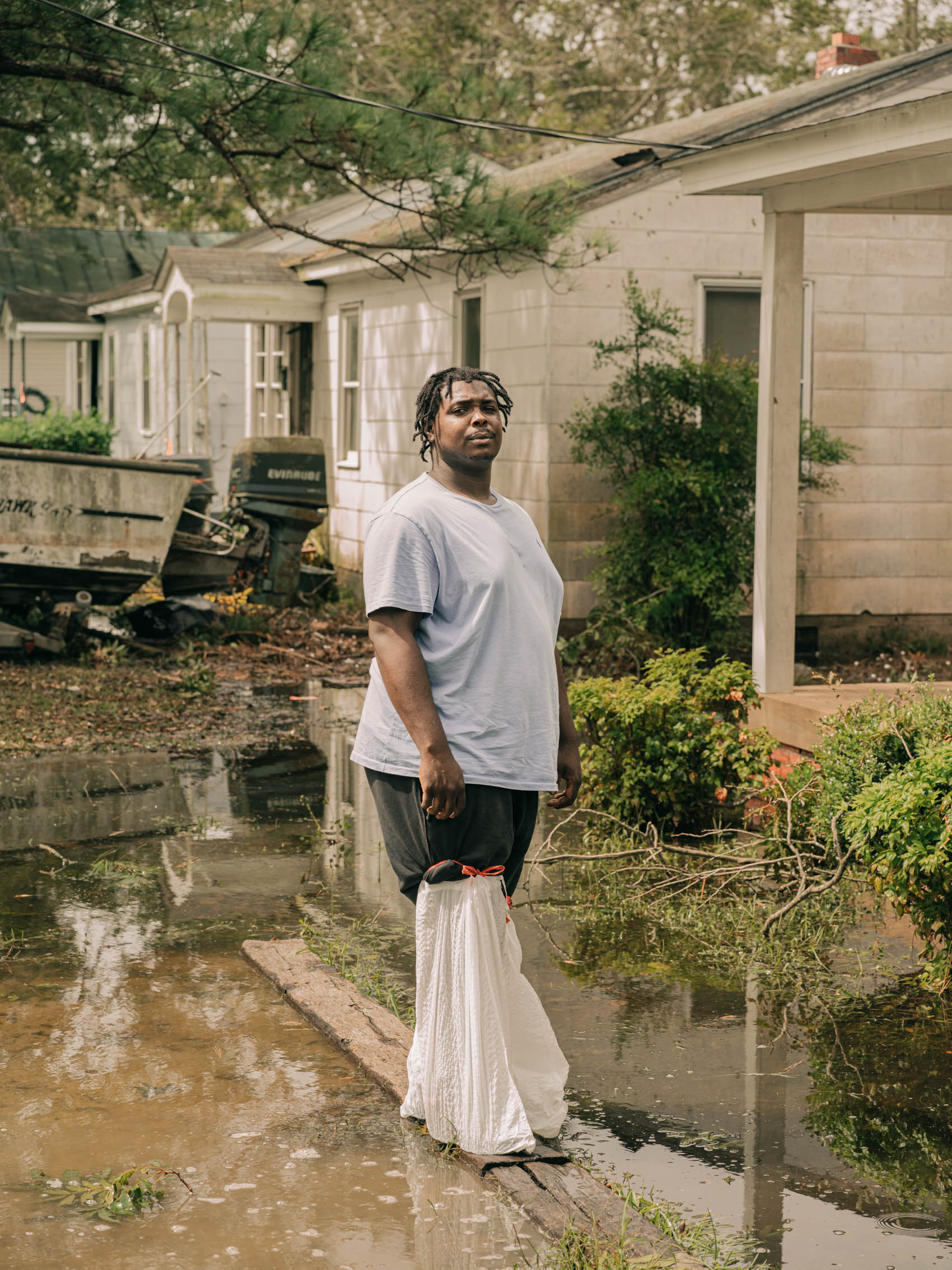 portrait of man with bags on feet after Hurricane Florence