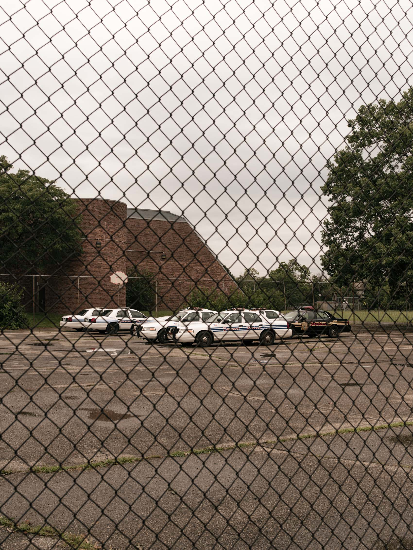 police cars behind chainlink fence