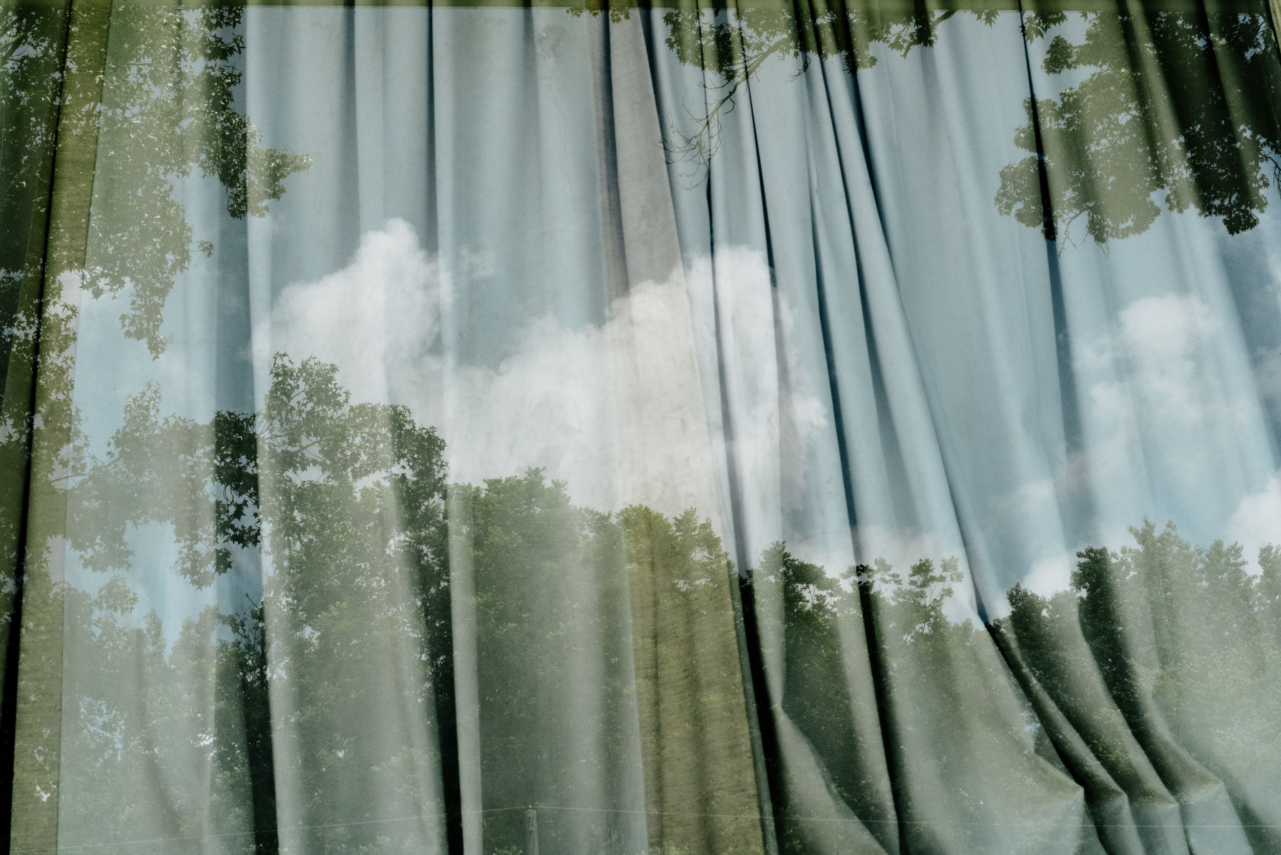 reflection of tree and sky in window with curtains